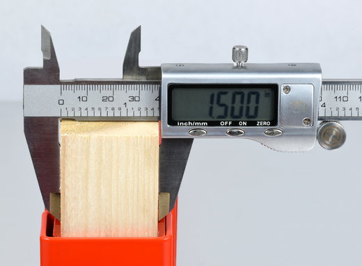 Caliper measuring a 1x2 to show actual width of 1.5 inches